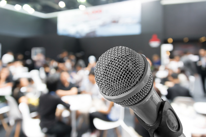 Microphone with blurred photo of conference